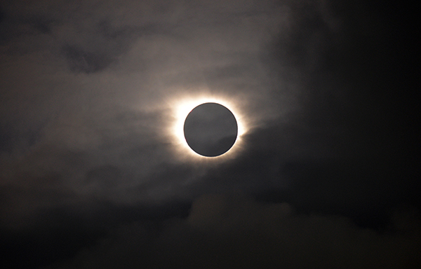 A total solar eclipse is visible through the clouds as seen from Vagar on the Faeroe Islands, Friday, March 20, 2015.  Apart from a few small breaks, a blanket of clouds in the Faeroe Islands blocked thousands of people there from experiencing the full effect of the total eclipse.  (AP Photo/Eric Adams)